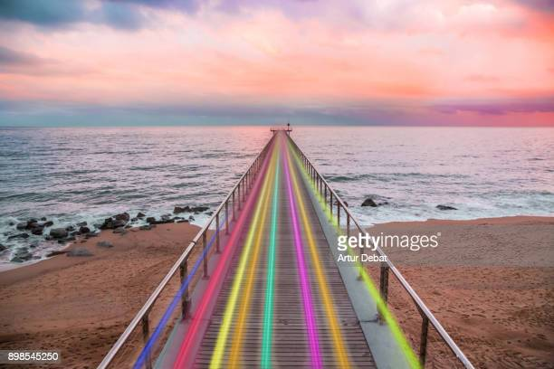 Beautiful rainbow created with light trails with high speed over nice vanishing perspective of a pier going over the Mediterranean Sea with sunset colors in a creative picture.