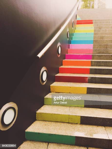 Beautiful rainbow steps in mall stairs in the city of Barcelona in contrast with black wall.
