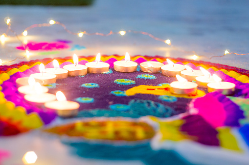 Beautiful rangoli made from colored powders and decorated with wax candle diyas on diwali eve 1166045311