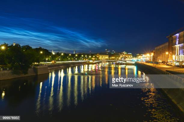 beautiful rare natural phenomenon of noctilucent clouds (night shining clouds) over central part of moscow. a small river in the foreground. shot at long exposure - light natural phenomenon stock pictures, royalty-free photos & images