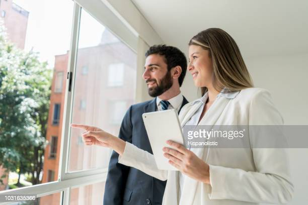 Beautiful real estate agent pointing at the view to customer both looking very happy