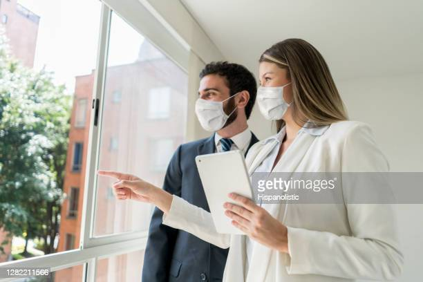 beautiful real estate agent pointing at the view to customer both looking very cheerful but wearing protective face masks - lease agreement stock pictures, royalty-free photos & images