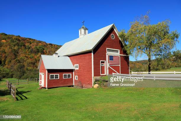 a beautiful red barn with a large american flag on the barn door in an autumn scenery - rainer grosskopf foto e immagini stock