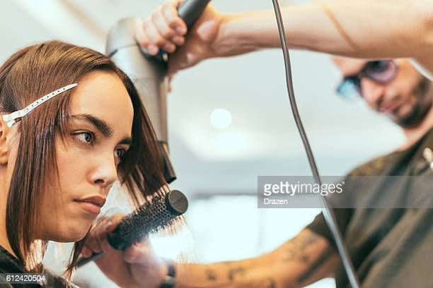 Beautiful red head woman in hair salon having hair cut