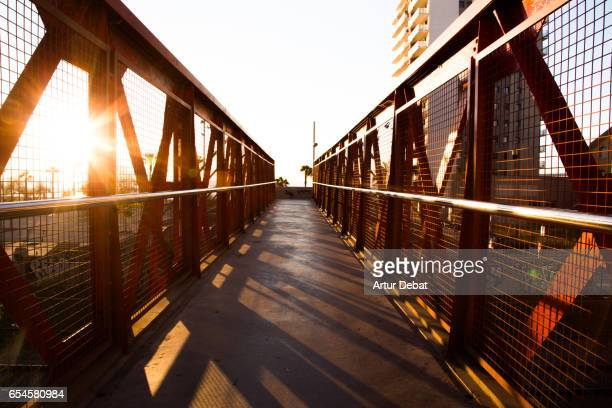 Beautiful red iron bridge in the Barcelona shoreline over railroad with urban style and nice vanishing point during sunrise with the cityscape and beach views.