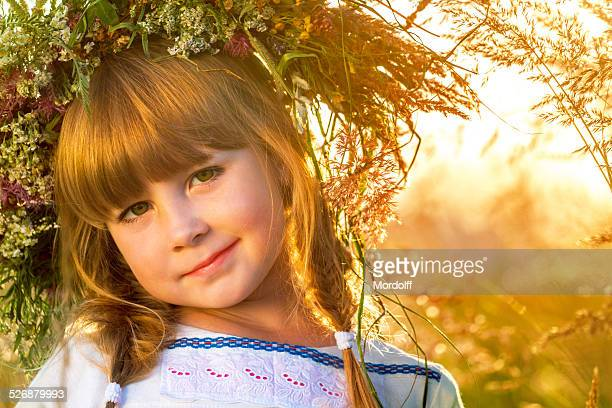 Beautiful red-haired little girl in wreath