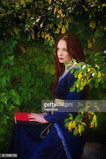 Beautiful redhead sitting with book in lap looking away.