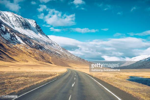 beautiful relax scenic view of the road with snow and mountain background in winter season , amazing view of road trip around iceland. - road trip stock pictures, royalty-free photos & images