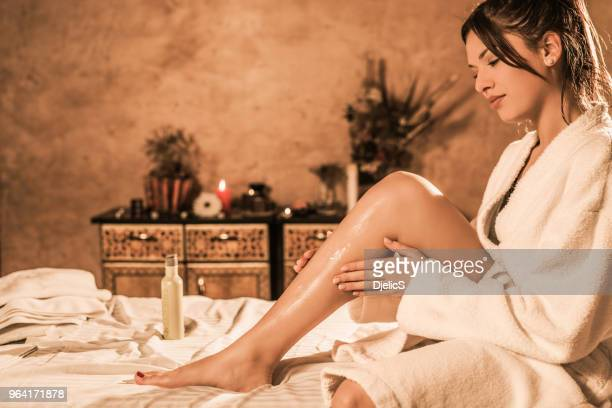 beautiful relaxed young woman in bathrobe putting lotion on her skin. - parte del corpo umano foto e immagini stock