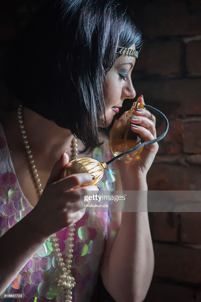Beautiful retro woman smells perfume bottle : Stock Photo