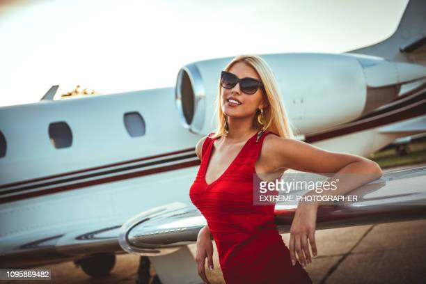 beautiful rich blonde woman leaning on a wing of a private airplane that is parked on a tarmac - millionnaire stock pictures, royalty-free photos & images