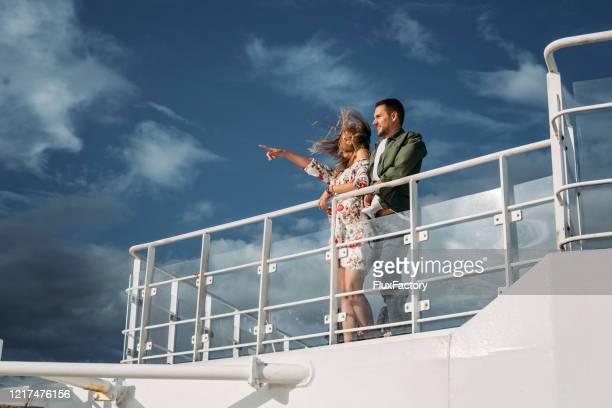 beautiful romantic couple looking at view from a cruise ship - ponte di una nave foto e immagini stock