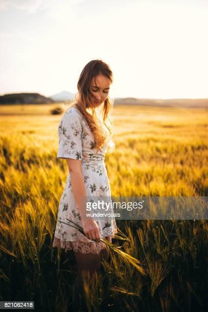 Hermosa mujer retra romántico permanente en campo de trigo al atardecer