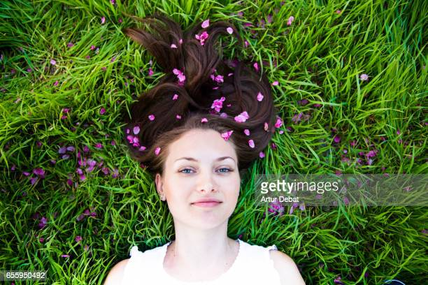 Beautiful russian girl laying on the grass with vivid colors and long hair covered with pink flowers during the springtime in the Catalonia countryside.