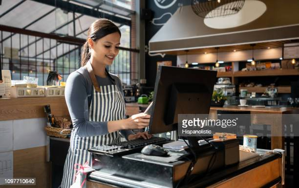 beautiful sales clerk at the cash register holding a phone and typing something on computer at the supermarket - checkers stock photos and pictures