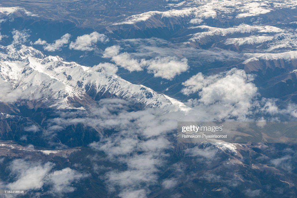 Beautiful sandstone Himalayan mountains with snow in summer season, Clouds and snow mountain, seen from airplane : Stock Photo