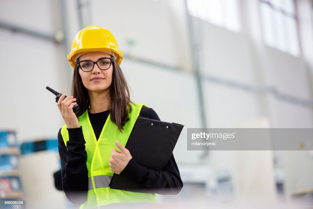 Beautiful satisfied young female in factory : Stock Photo