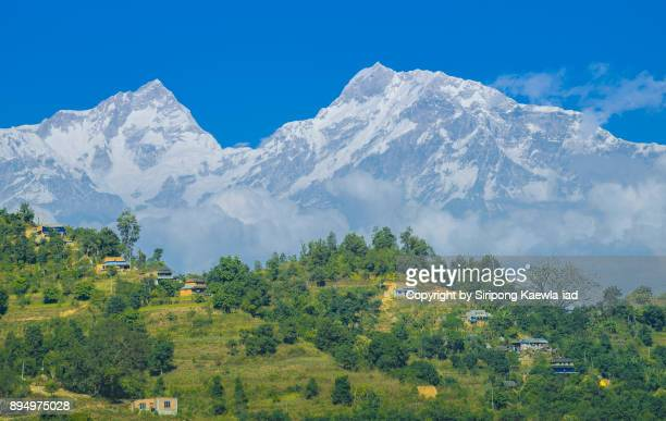 Beautiful scenery of small village with the Annapurna mountain range in background during the way to Pokhara city, Nepal.