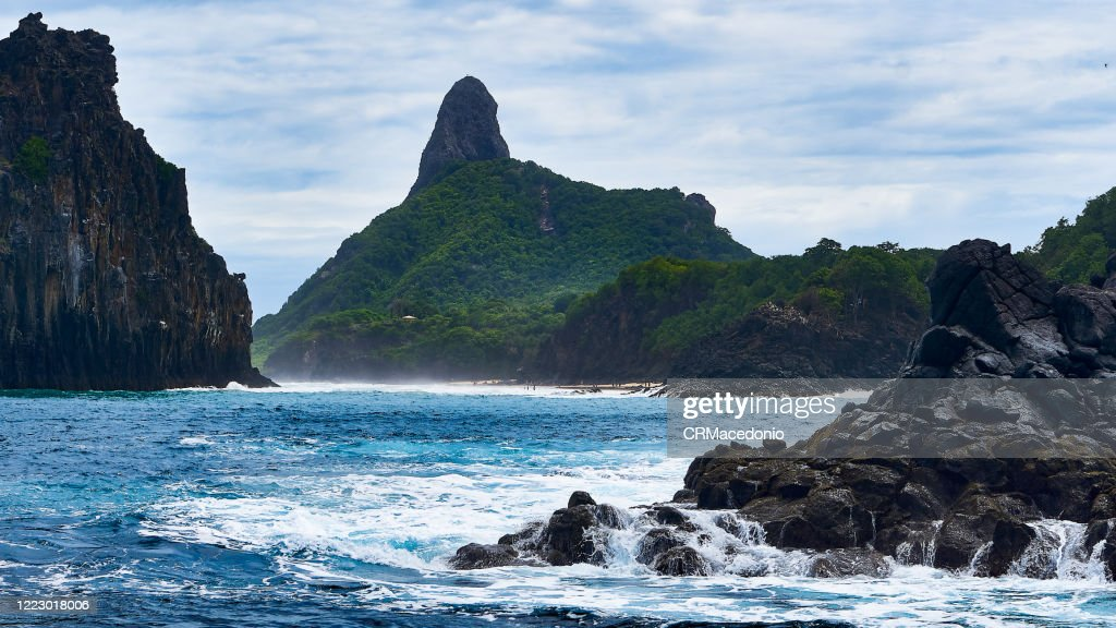 Beautiful scenery, we have Morro Dois Irmãos on the left, Baia dos Porcos on the right, Morro do Pico in the background and dozens of surfers in the middle of Praia da Cacimba do Padre. : Stock Photo
