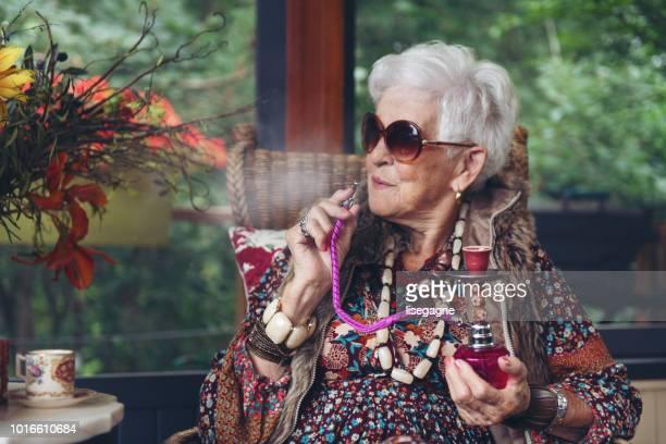 beautiful senior boho stylish woman - hookah stock photos and pictures