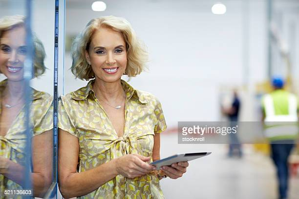 Beautiful senior businesswoman in factory with digital tablet
