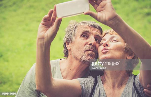 Beautiful senior caucasian couple taking selfie - duck face