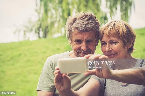 Beautiful senior caucasian couple taking selfie, outdoor portrait