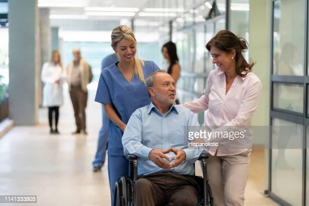 Hermosa pareja de ancianos en el hospital, hombre sentado en silla de ruedas y enfermera de pie detrás de todo hablar y sonreír