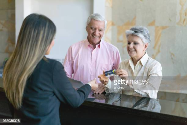 Beautiful senior couple doing check in at hotel and senior woman handing a loyalty rewards card to receptionist all looking very happy
