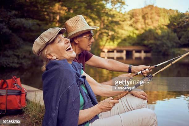 beautiful senior couple enjoying on the lake fishing and having fun - fishing stock pictures, royalty-free photos & images