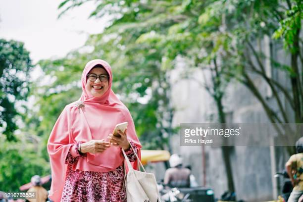 beautiful senior islam woman with mobile phone - indonesia stock pictures, royalty-free photos & images