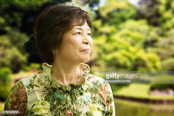 Beautiful senior Japanese woman enjoying a visit to park