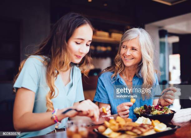 beautiful senior mother and daughter eating lunch together at restaurant - mother's day stock pictures, royalty-free photos & images