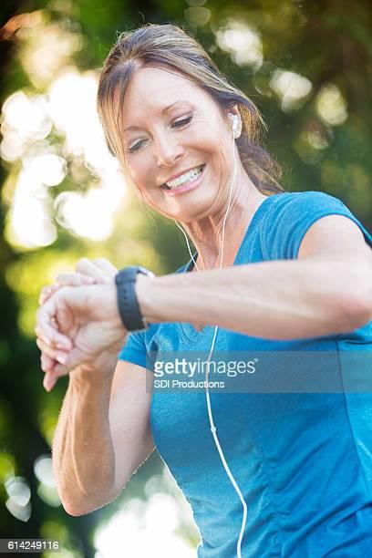 Beautiful senior woman checks fitness tracker