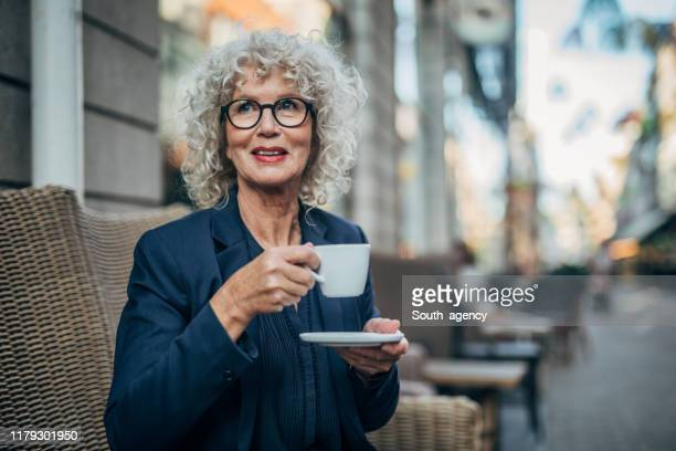 beautiful senior woman drinking a hot drink - working seniors stock pictures, royalty-free photos & images
