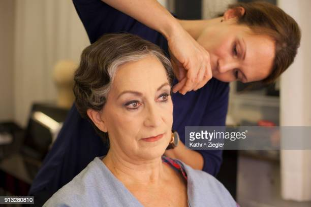 Beautiful senior woman having her hair and makeup done by makeup artist before stage performance