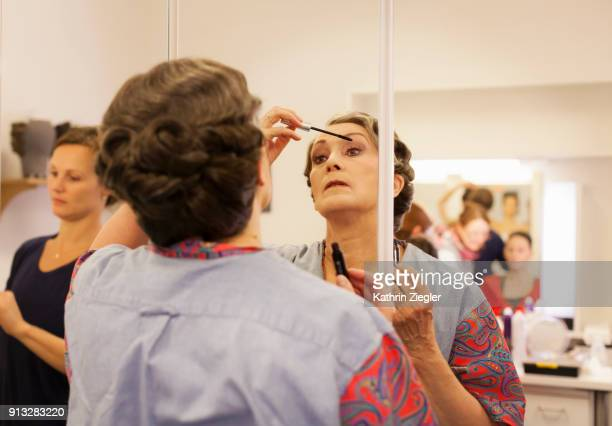 Beautiful senior woman in dressing room applying mascara before going on stage