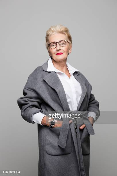 beautiful senior woman in grey overcoat - hands in pockets stock pictures, royalty-free photos & images