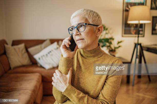 beautiful senior woman is talking on the phone in the living room - worried stock pictures, royalty-free photos & images