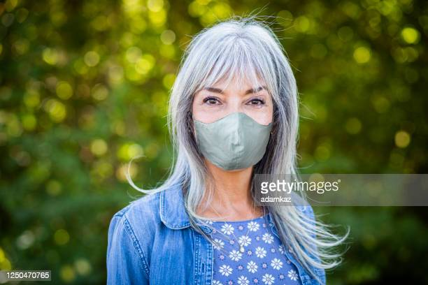 beautiful senior woman outdoors wearing a mask - white jacket stock pictures, royalty-free photos & images