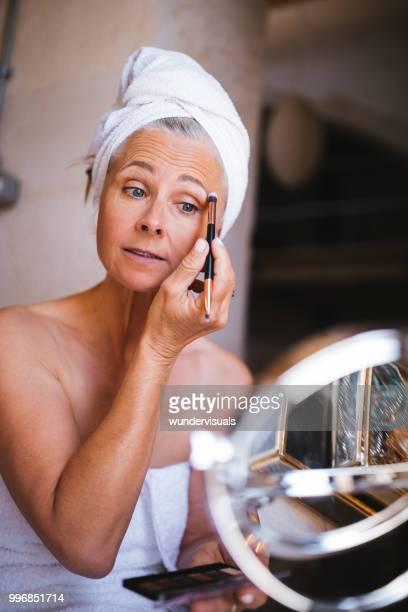 linda mulher sênior colocando maquiagem e aplicação da sombra - sombra maquiagem de olho - fotografias e filmes do acervo