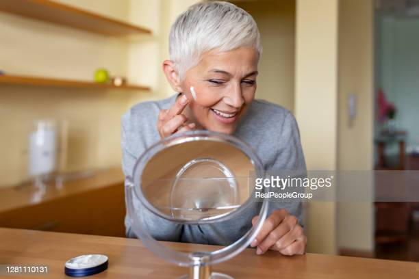 beautiful senior woman putting on the cream. - white hair stock pictures, royalty-free photos & images