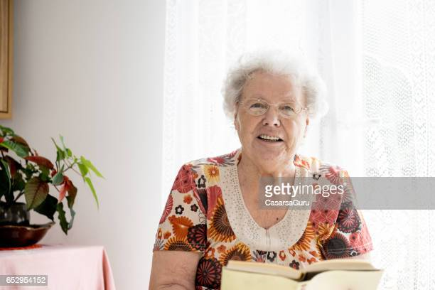 Beautiful Senior Woman Reading In Her Bedroom At The Nursery Home