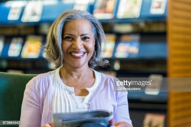 Beautiful senior woman reading magazine in library