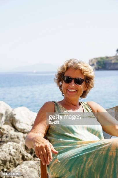 Beautiful senior woman relaxing in cafe by the  sea.