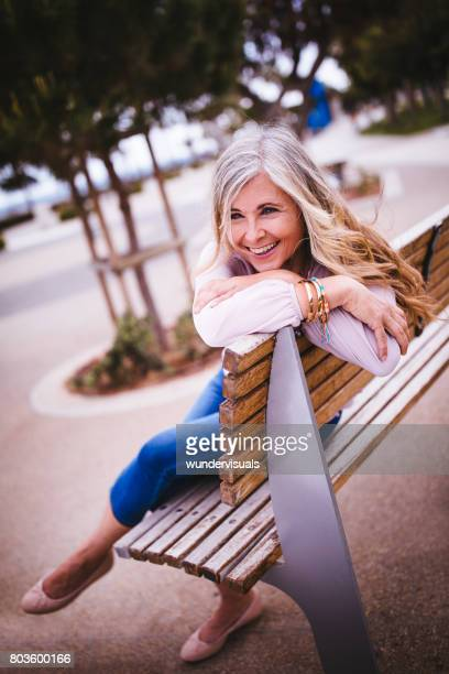 Beautiful senior woman relaxing sitting on park bench