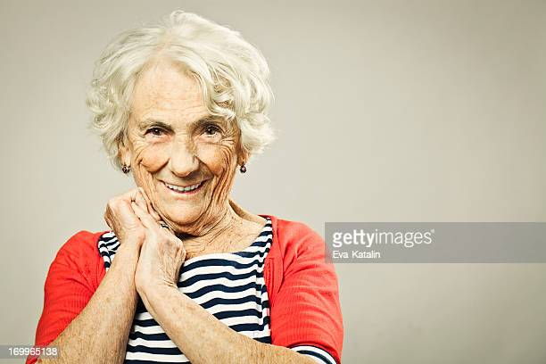 beautiful senior woman smiling at camera - old woman stock photos and pictures