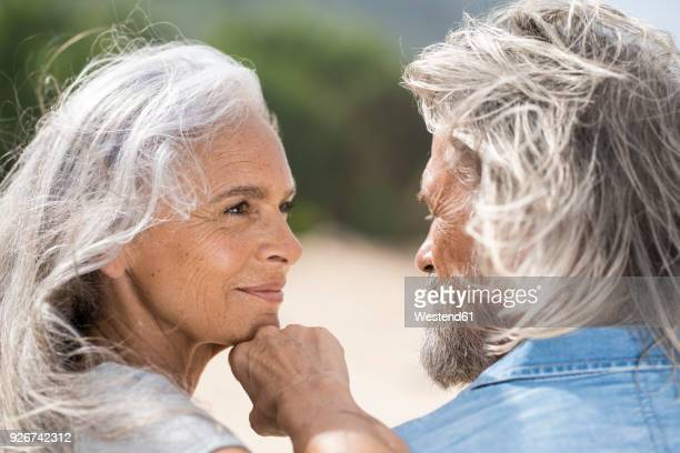 Beautiful senior woman smiling at her husband