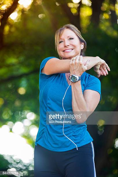 Beautiful senior woman stretches before exercising