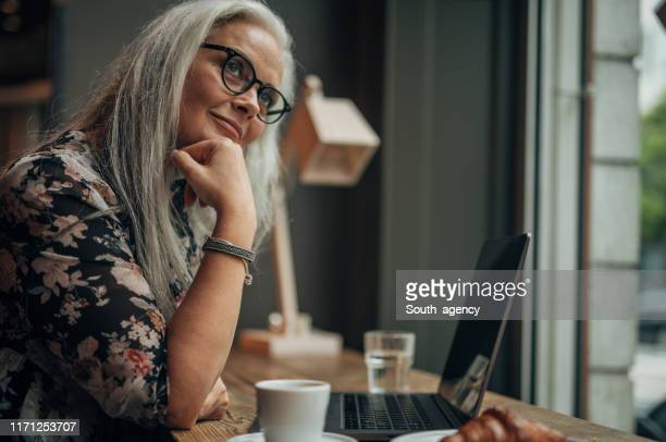 beautiful senior woman working on laptop while drinking coffee - gray hair stock pictures, royalty-free photos & images